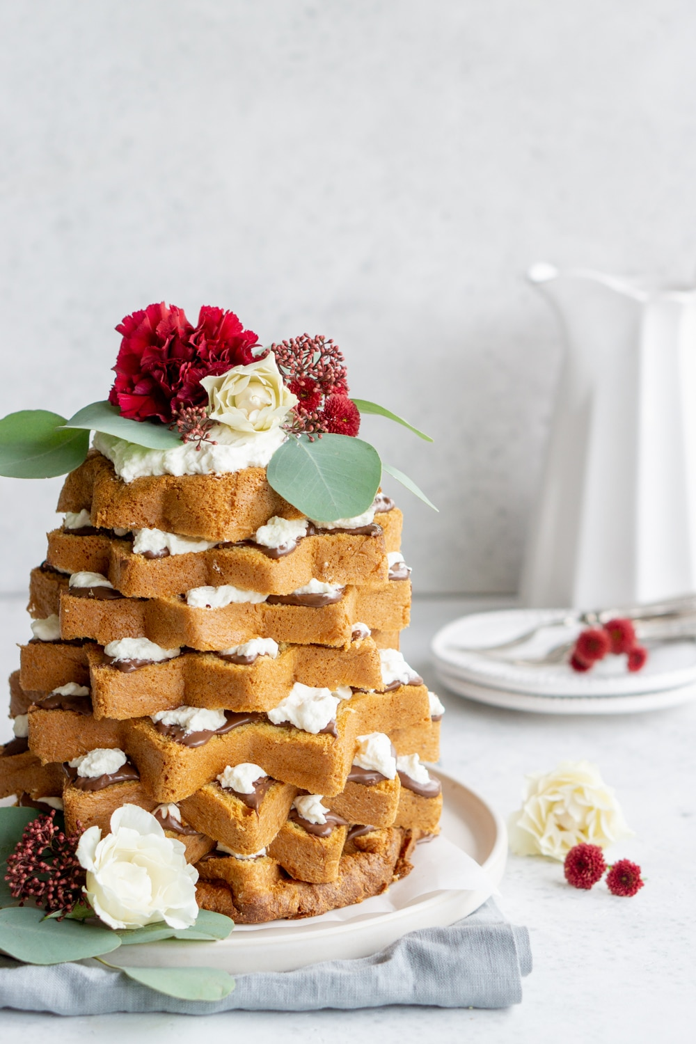 Pandoro Christmas tree cake with flowers on top and a vase in the background