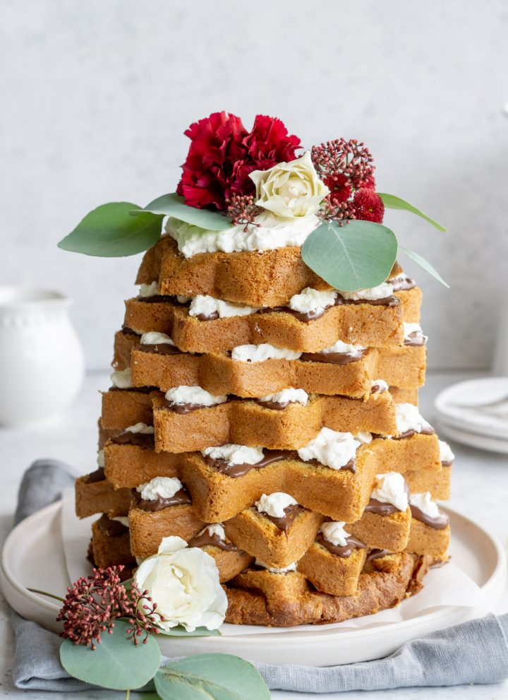 Pandoro christmas tree cake with nutella topped with fresh flowers