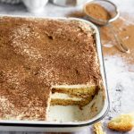Front angle view of pandoro tiramisu with cocoa powder in the background