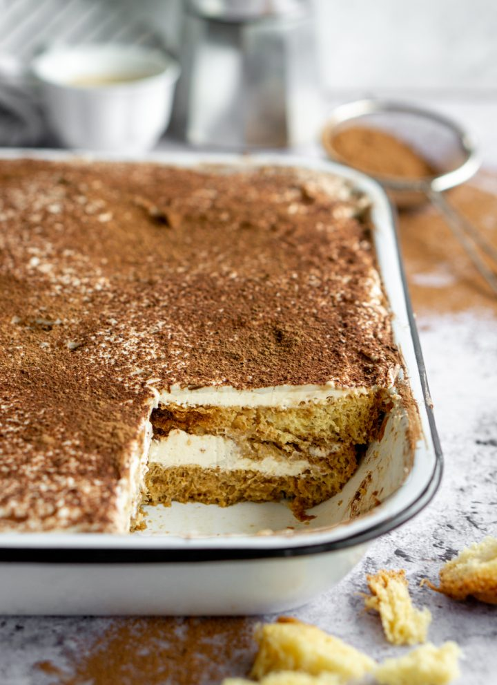 Pandoro tiramisu in a white pan with cocoa powder in the background