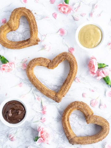 3 heart shaped churros on a marble background with pink flowers