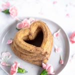 heart shaped churros stacked on a plate with pink flowers