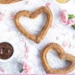 overhead shot of three heart churros with pink flowers