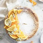 Pastiera napoletana decorated with fresh oranges, lemon and white flowers