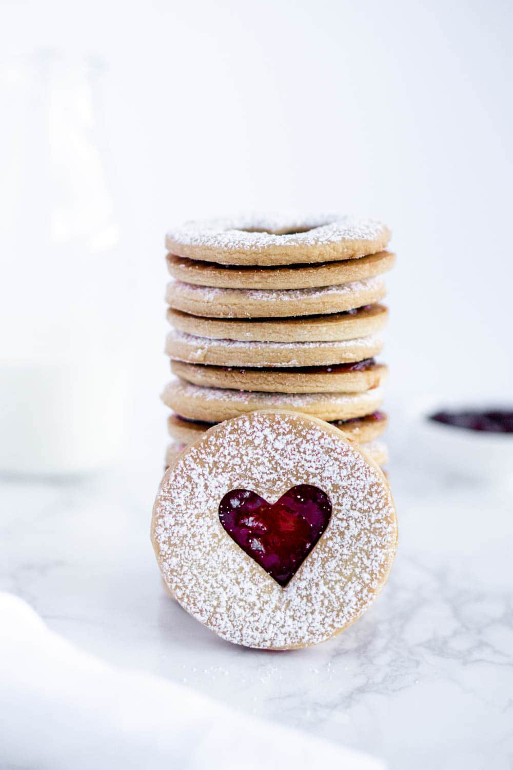 A stack of jam cookies with one jam cookie in front of the stack, with milk in the background