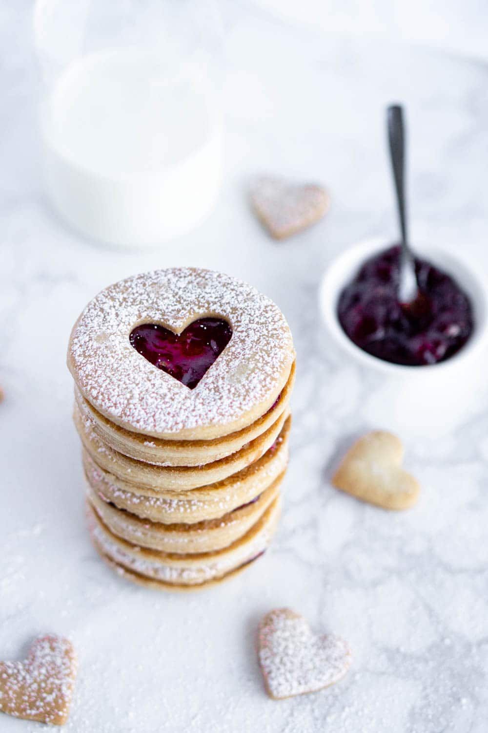 Stack of jam cookies with jam in the background