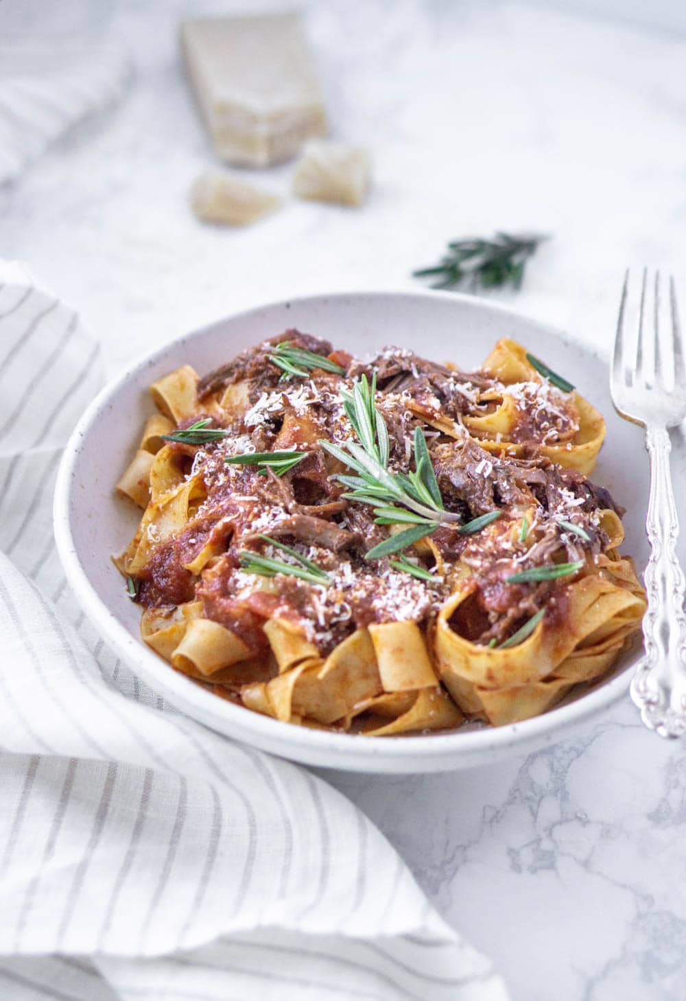 beef short rib pappardelle in a white plate with parmesan and rosemary in the background