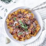 pappardelle with beef short rib ragu in a plate topped with rosemary
