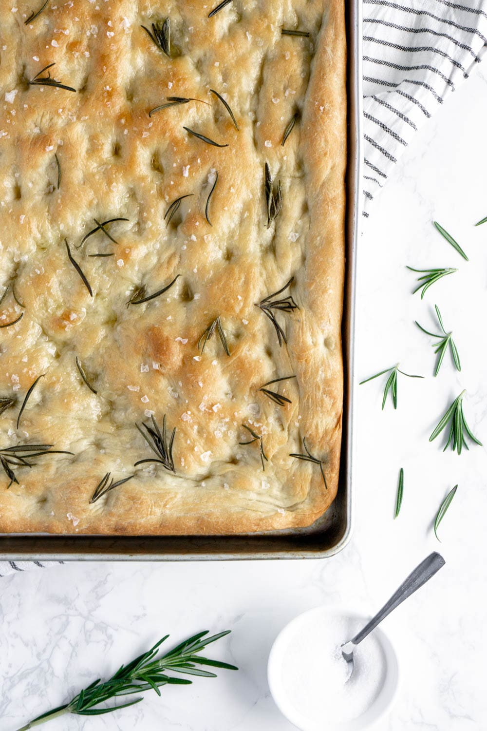 focaccia topped with rosemary in a sheet pan
