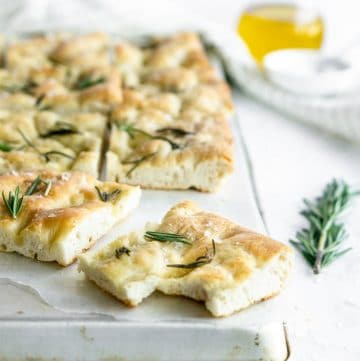 slice of focaccia with rosemary, olive oil and salt in the background