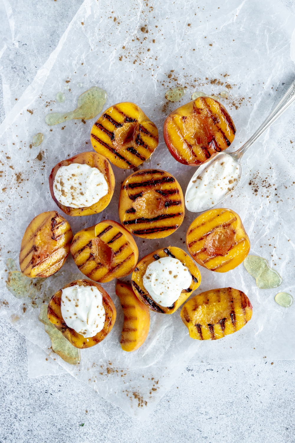 Cluster of grilled peaches with topped with ricotta and a spoon