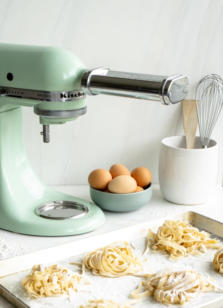 KitchenAid mixer with pasta attachment with homemade pasta in the foreground
