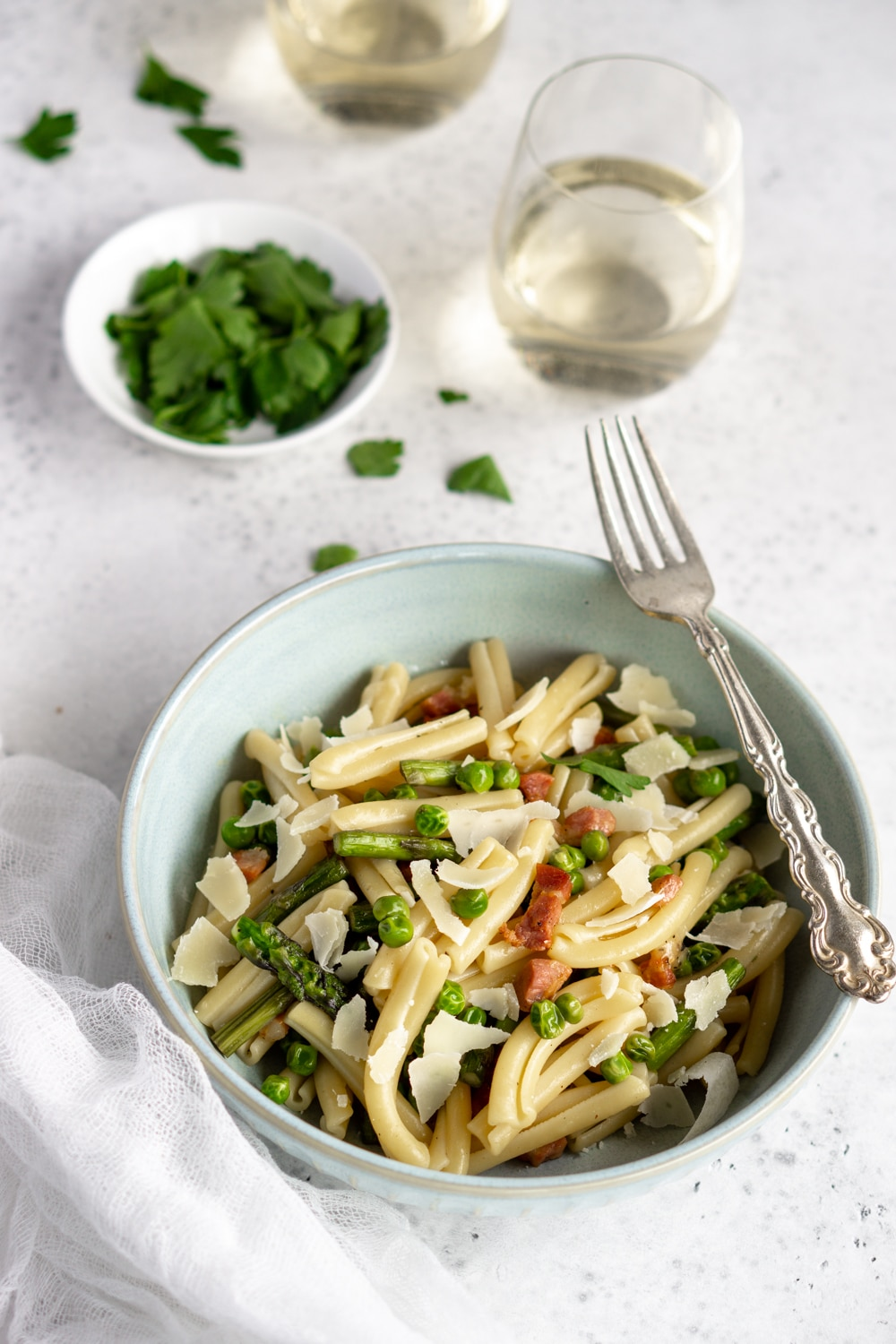 asparagus pasta with pancetta and peas with parslry and a glass of wine in the background