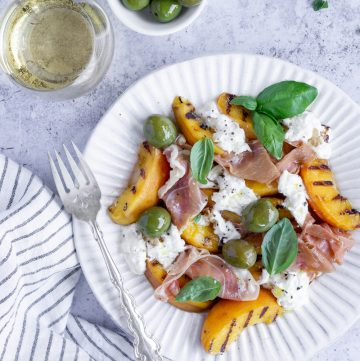peach salad with prosciutto and burrata with a napkin to the side
