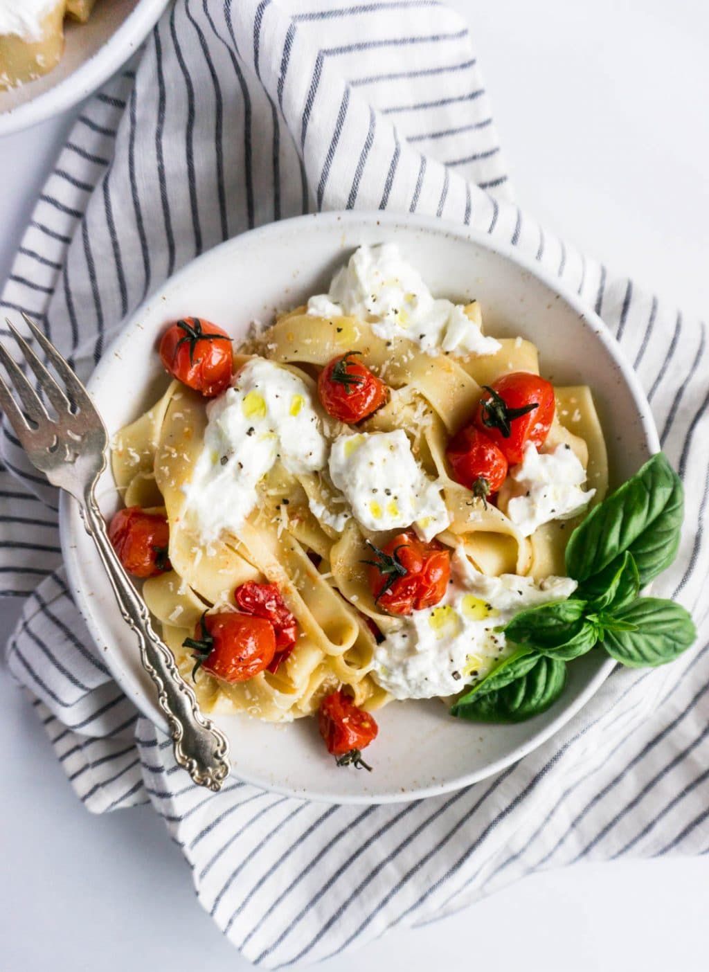 Bowl of pappardelle pasta with cherry tomato and burrata sauce with a striped napkin