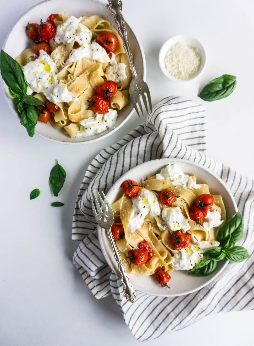 Two bowls of cherry tomato pasta with burrata, and a small bowl of parmesan to the side