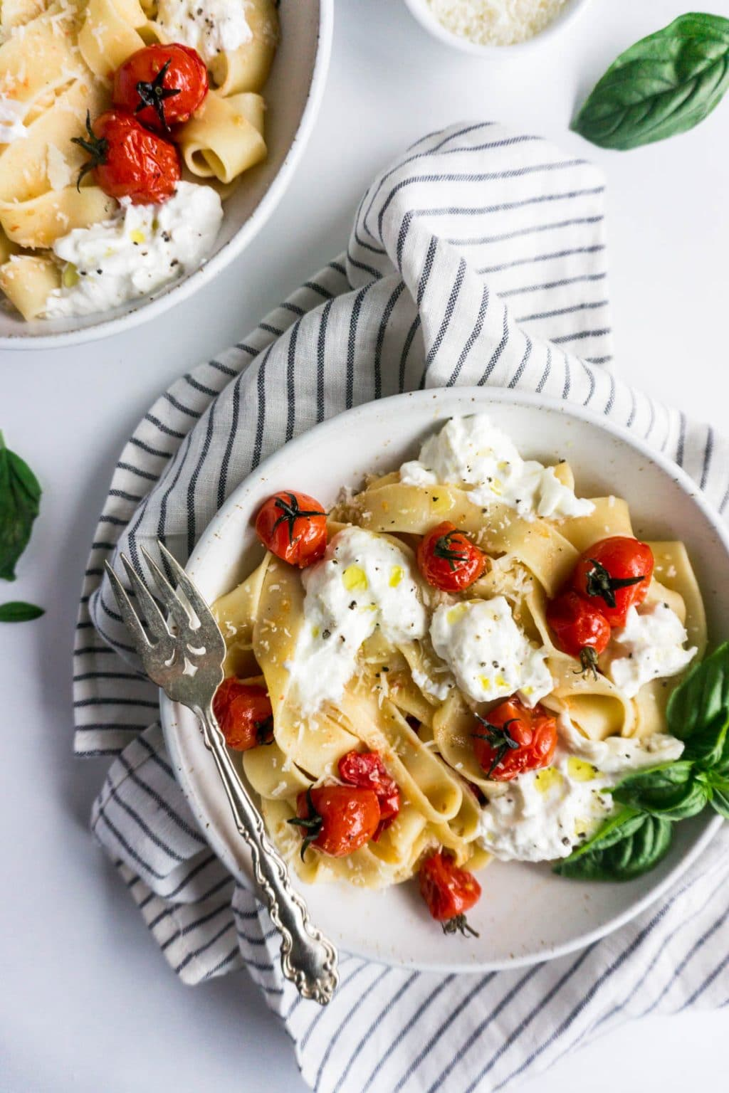 Burst cherry tomato pasta with burrata in a plate garnished with fresh basil