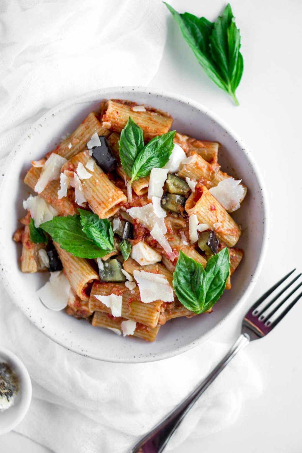 Eggplant pasta in a plate topped with fresh basil on a napkin