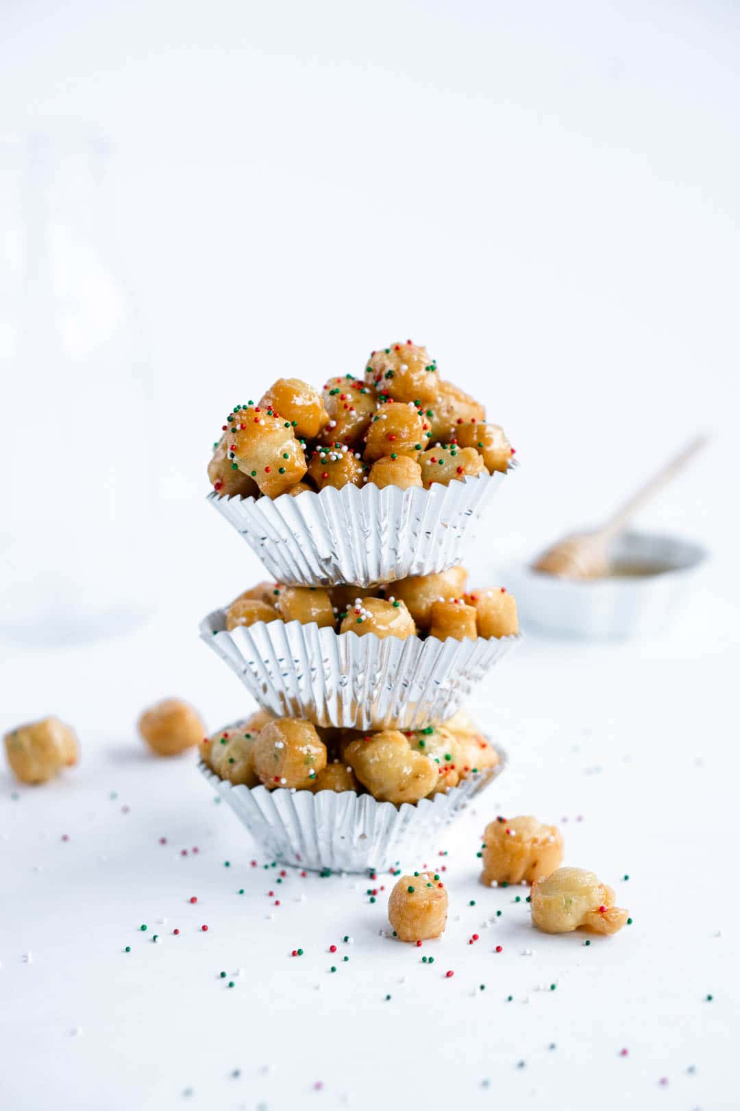 Stack of Struffoli Italian Christmas honey balls in individual muffin liners
