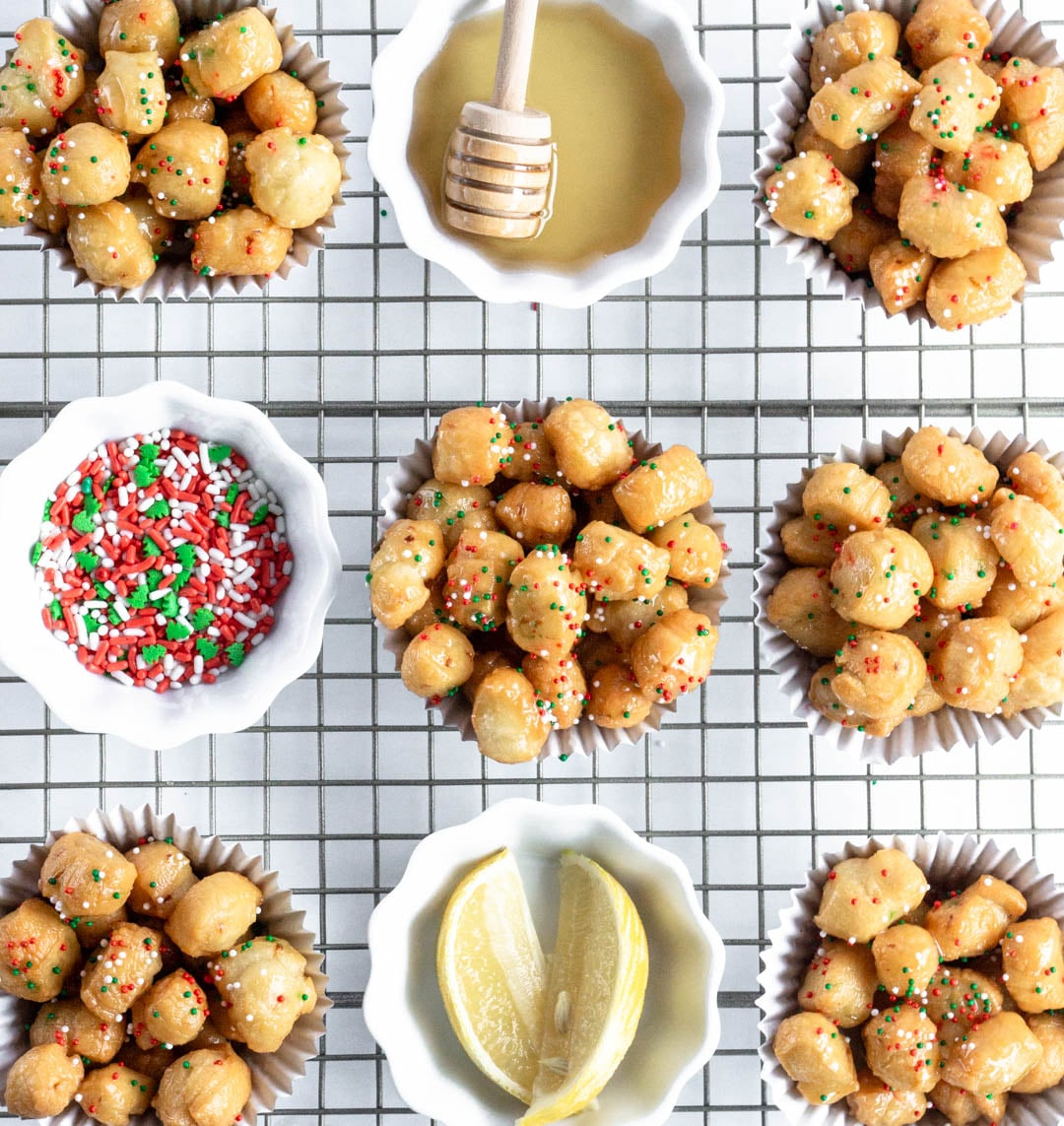 Overhead photo of struffoli on a cooling rack in individual muffin liners