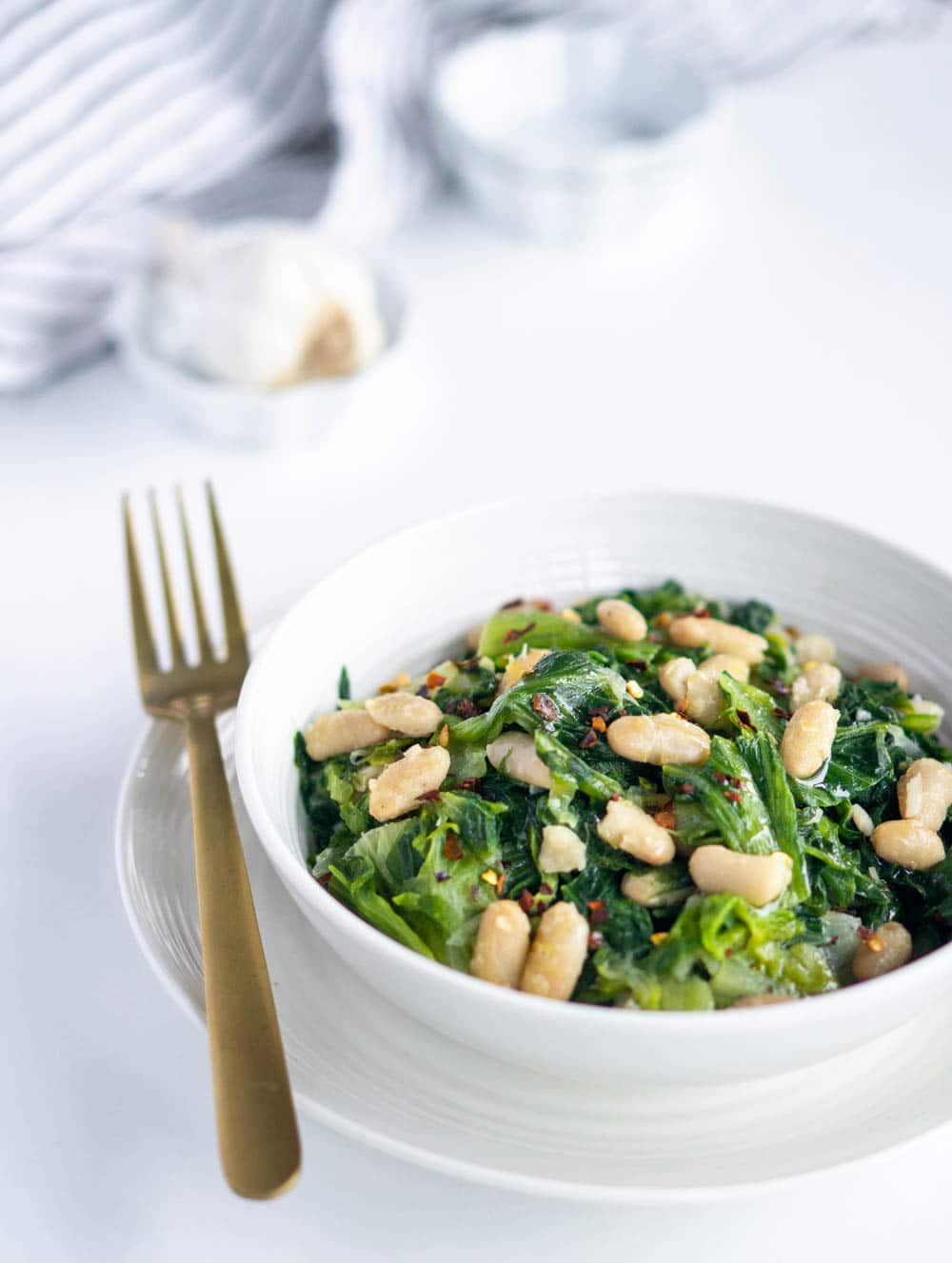 Side view of a dish of escarole and beans with garlic in the background