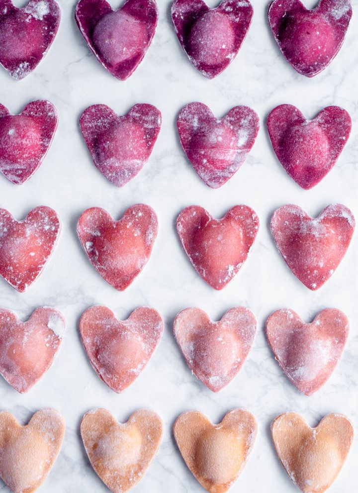 Overhead shot of ombré beet ravioli hearts on a marble background