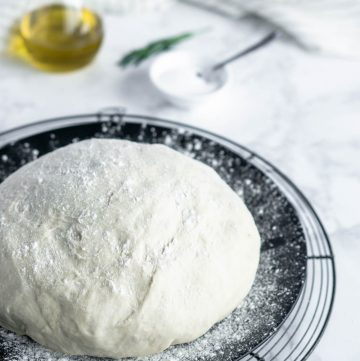 pizza dough on a black plate with olive oil and rosemary in the background