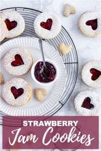 Overhead shot of strawberry linzer cookies on a plate and cooling rack