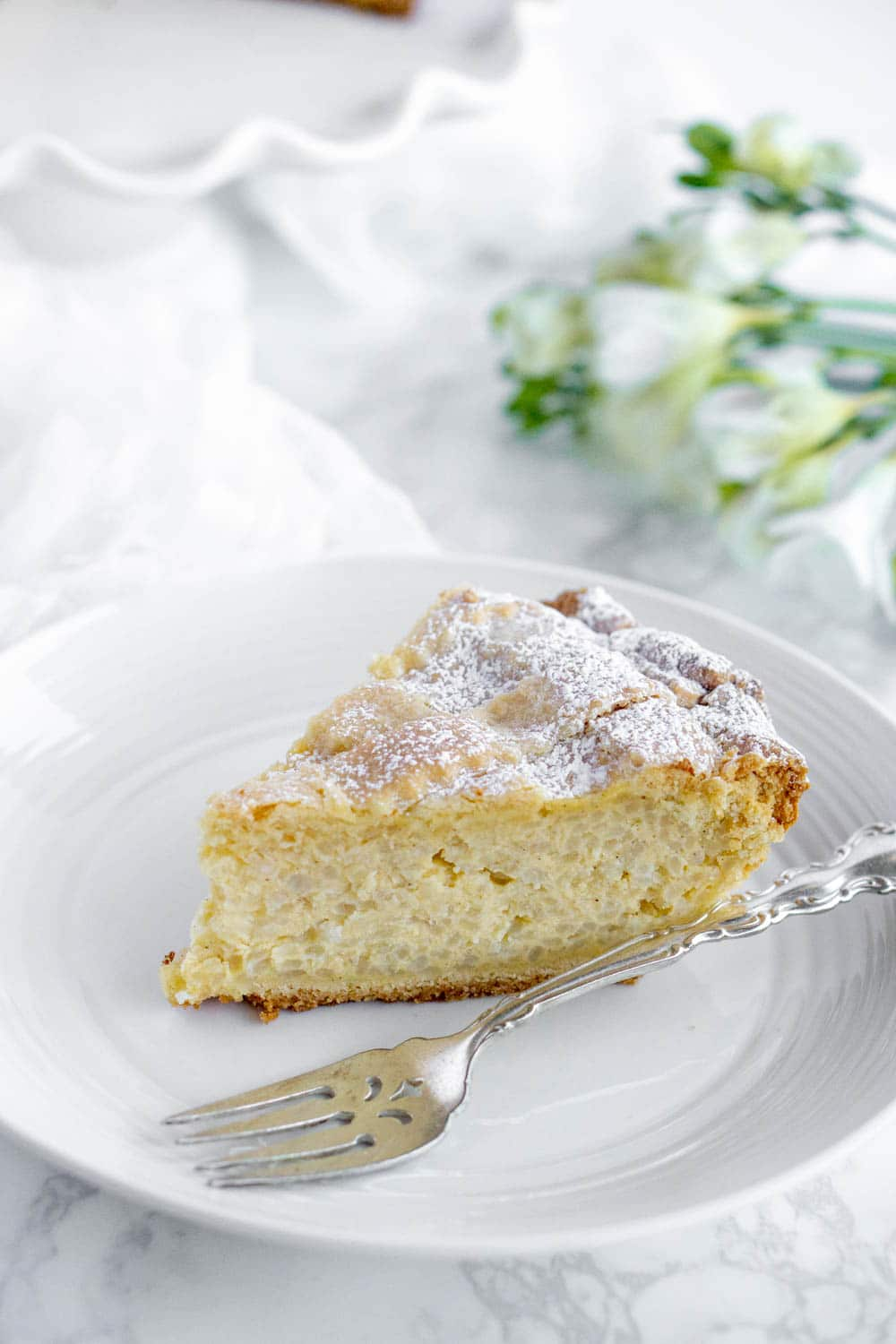 Slice of Italian Easter rice pie on a plate with flowers in the background