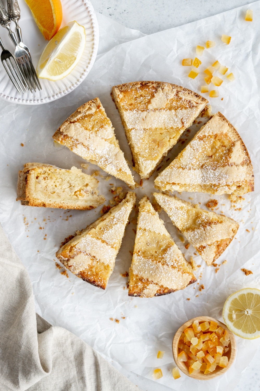 Pastiera napoletana cut into 7 slices with a lemon and candied oranges to the side