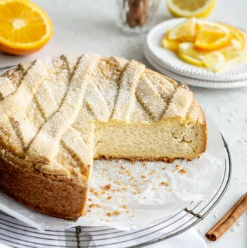 A sweet Easter rice pie sitting on a cooling rack with oranges and cinnamon sticks in the background