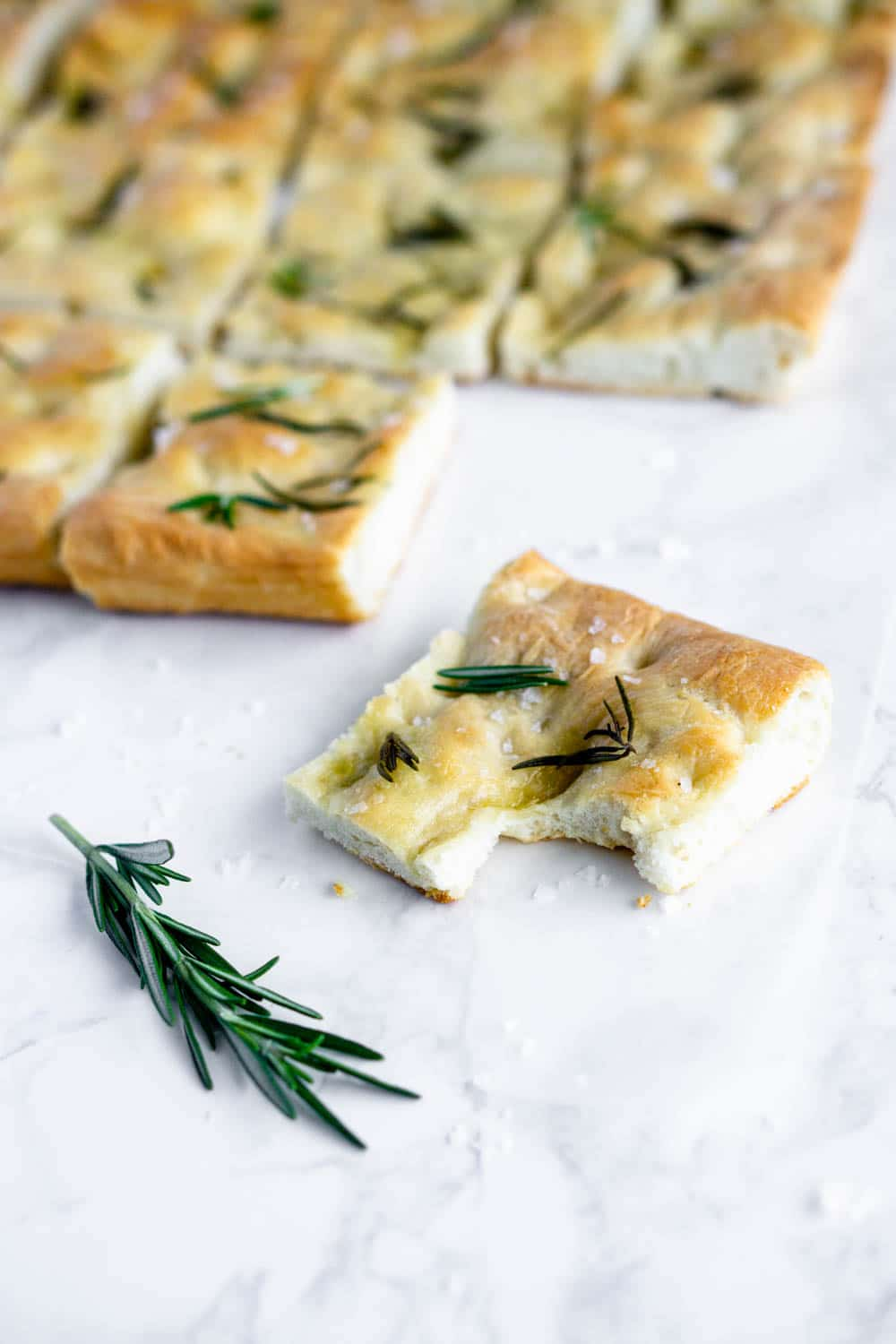 square slice of focaccia topped with rosemary and focaccia in the background