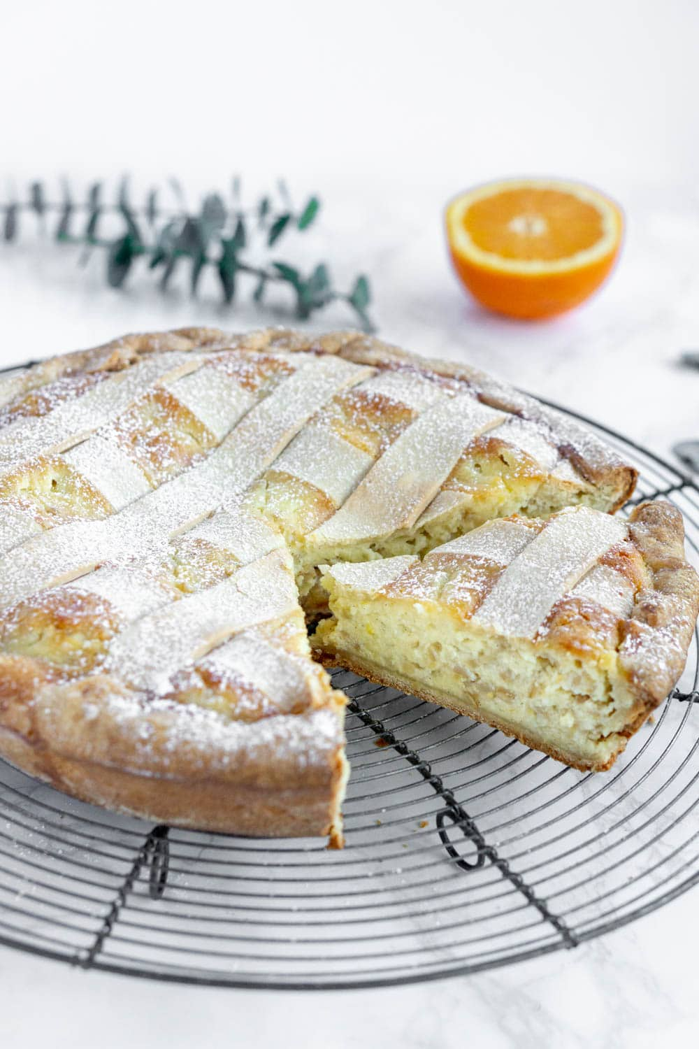 side photo of pastiera napoletana with orange in the background