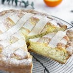 side angle photo of pastiera napoletana on a cooling rack with an orange in the background