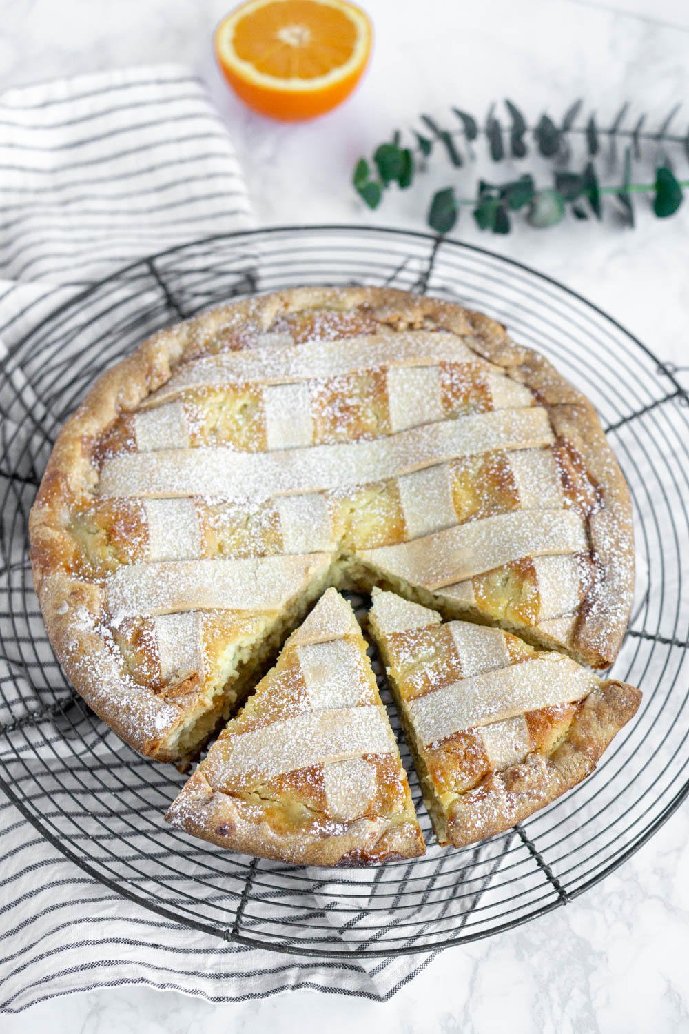 overhead photo of pastiera napoletana with two slices cut out of it