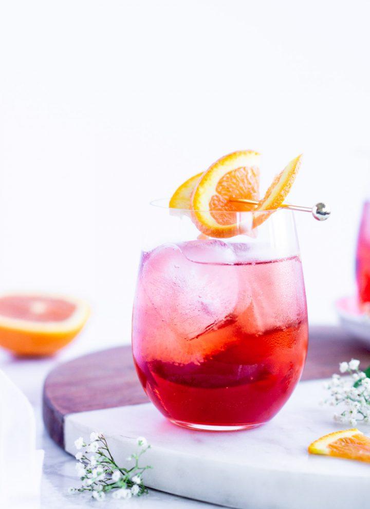 campari spritz in a glass garnished with an orange