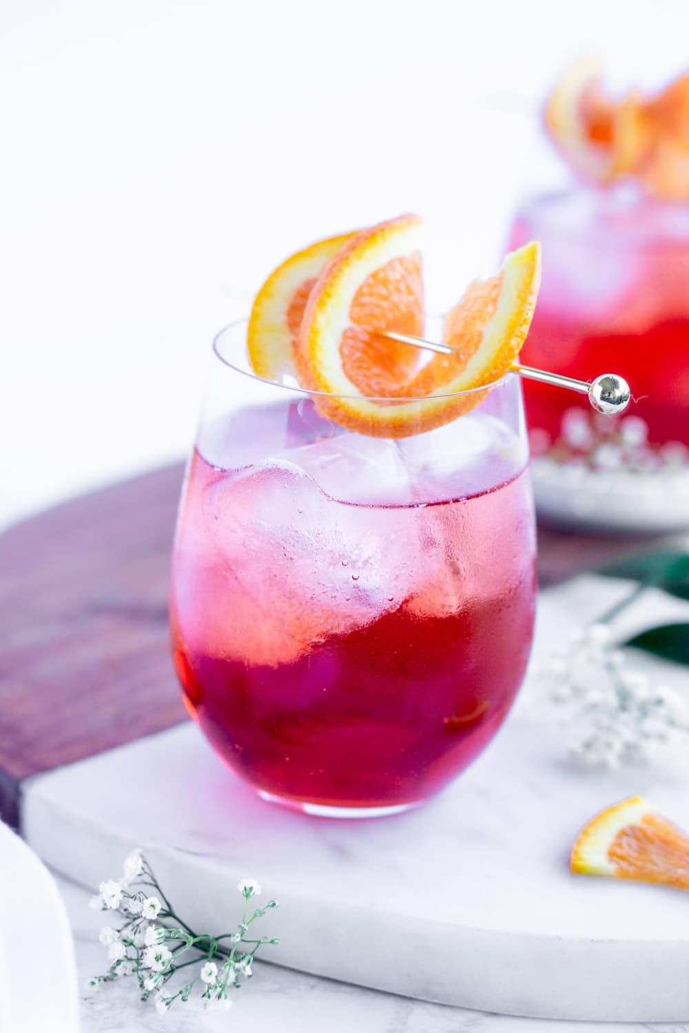 campari spritz cocktail with ice in a stemless wine glass garnished with an orange