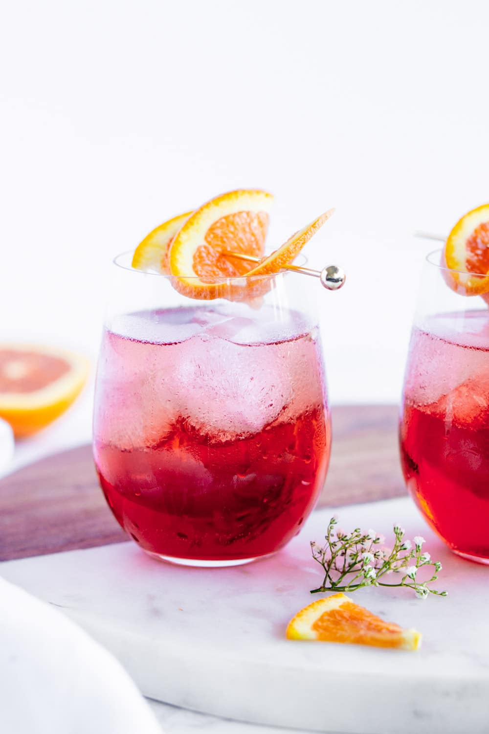 2 campari spritz cocktails on a marble serving board