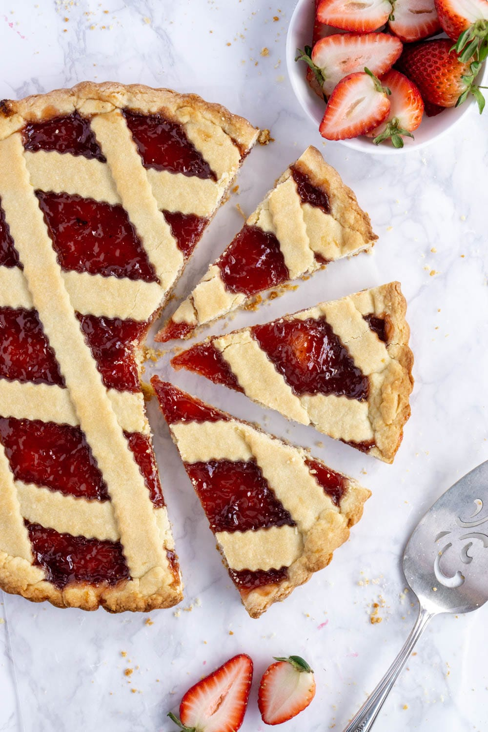 overhead photo of a jam crostata with 3 slices cut out of it