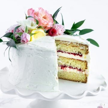 raspberry limoncello cake on a white cake stand with a slice cut out