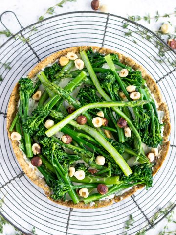 Asparagus tart on a cooling rack surrounded by thyme