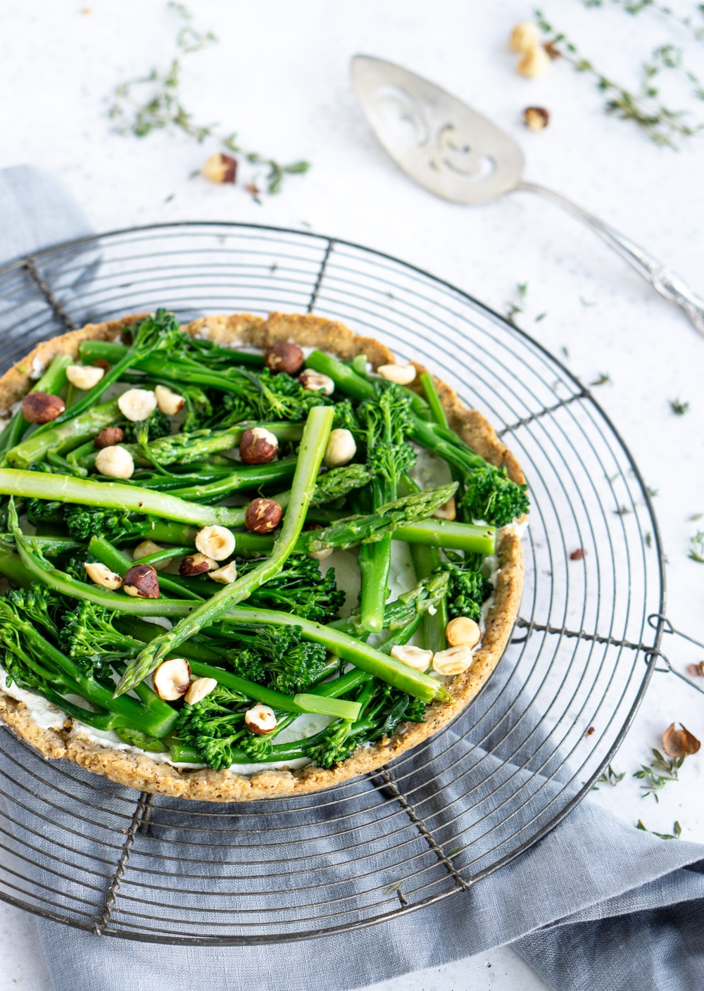Side view of asparagus tart with a serving spoon in the background