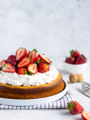 olive oil cake topped with mascarpone cream and sliced prosecco strawberries, and a bowl of strawberries in the background