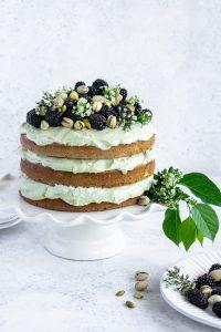 pistachio cake on a white cake stand