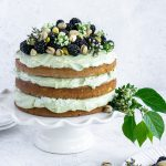 pistachio cake on a white cake stand