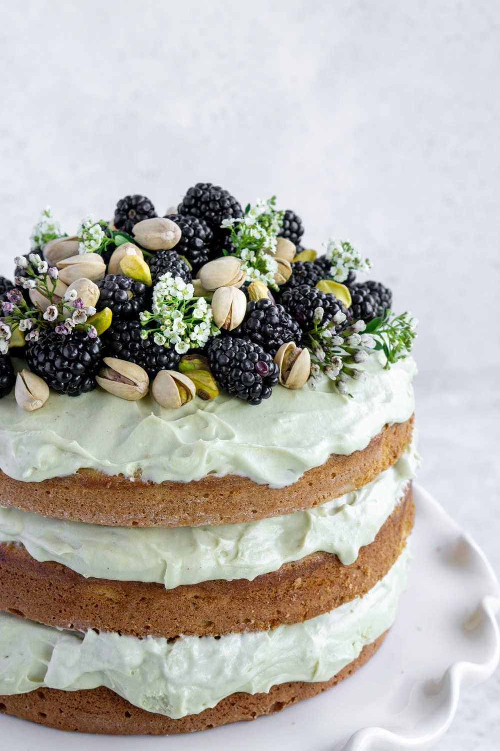 side view of layered pistachio cake topped with flowers, blackberries and pistachios