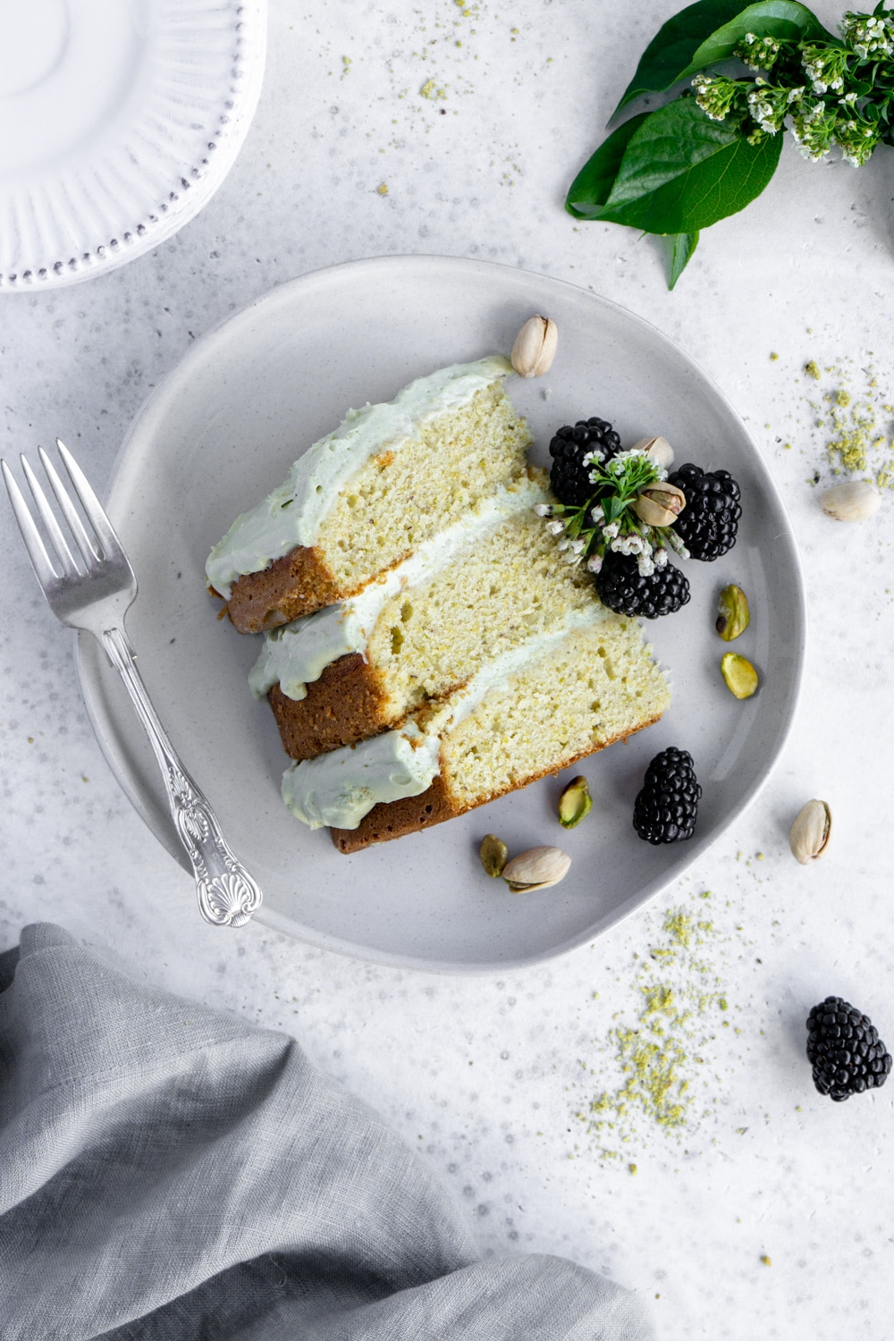 slice of pistachio cake on a plate with blackberries around it