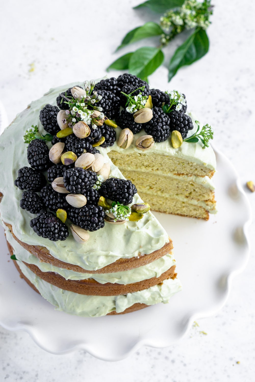 pistachio cake on a plate topped with blackberries and pistachios