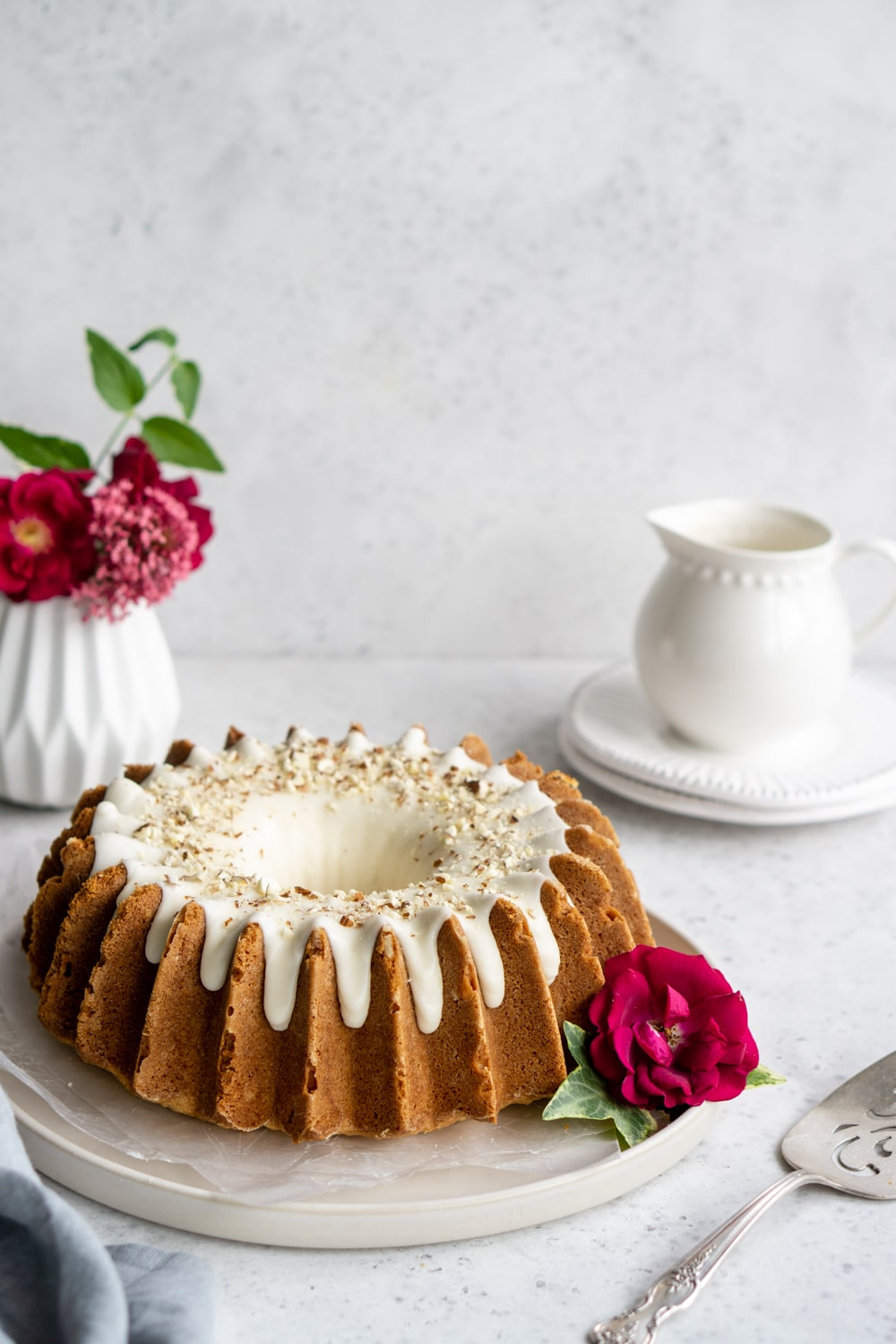 almond bundt cake on a plate with flowers in the background