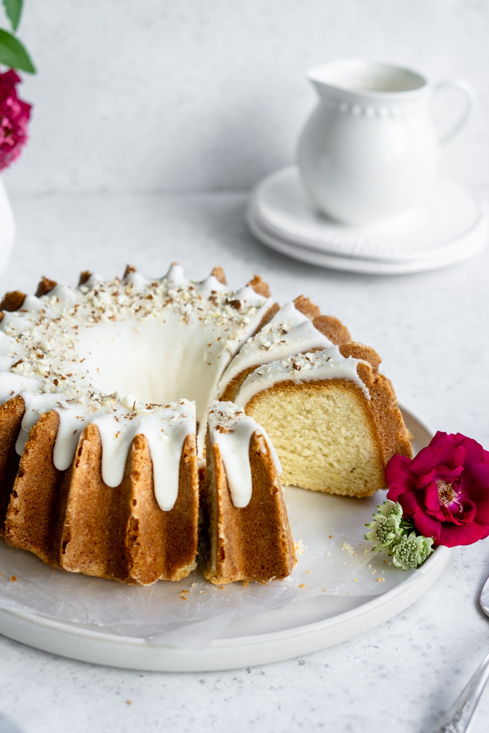 almond bundt cake on a plate with a slice taken out